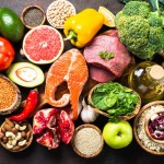 A selection of organic food for healthy nutrition, superfoods. Meat, fish, legumes, nuts, seeds, greens, oil and vegetables. Top view on a dark stone table.