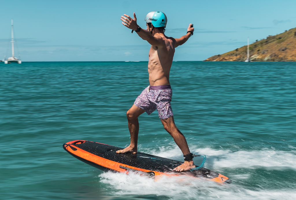 Radinn GX2 Jetboard with a man riding on the ocean and a catamaran in the background